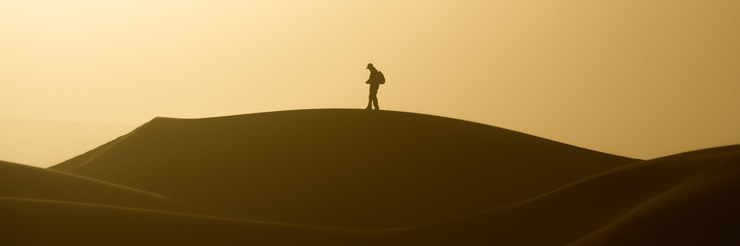 A photographer standing on a dune in a desert