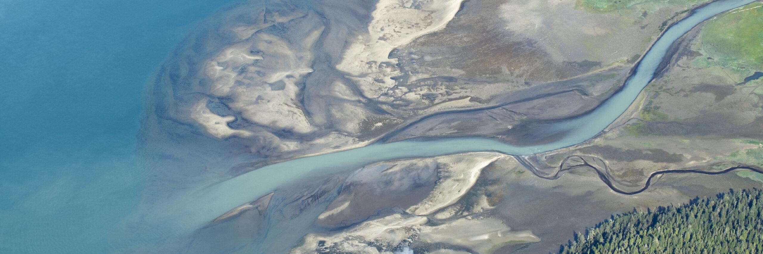 a glacier river flowing into the blue ocean